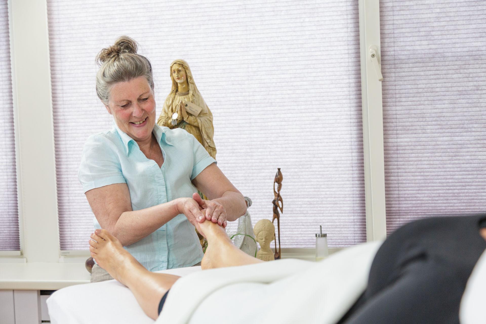 Silvia geeft voetreflexologie aan een vrouw in de overgang
